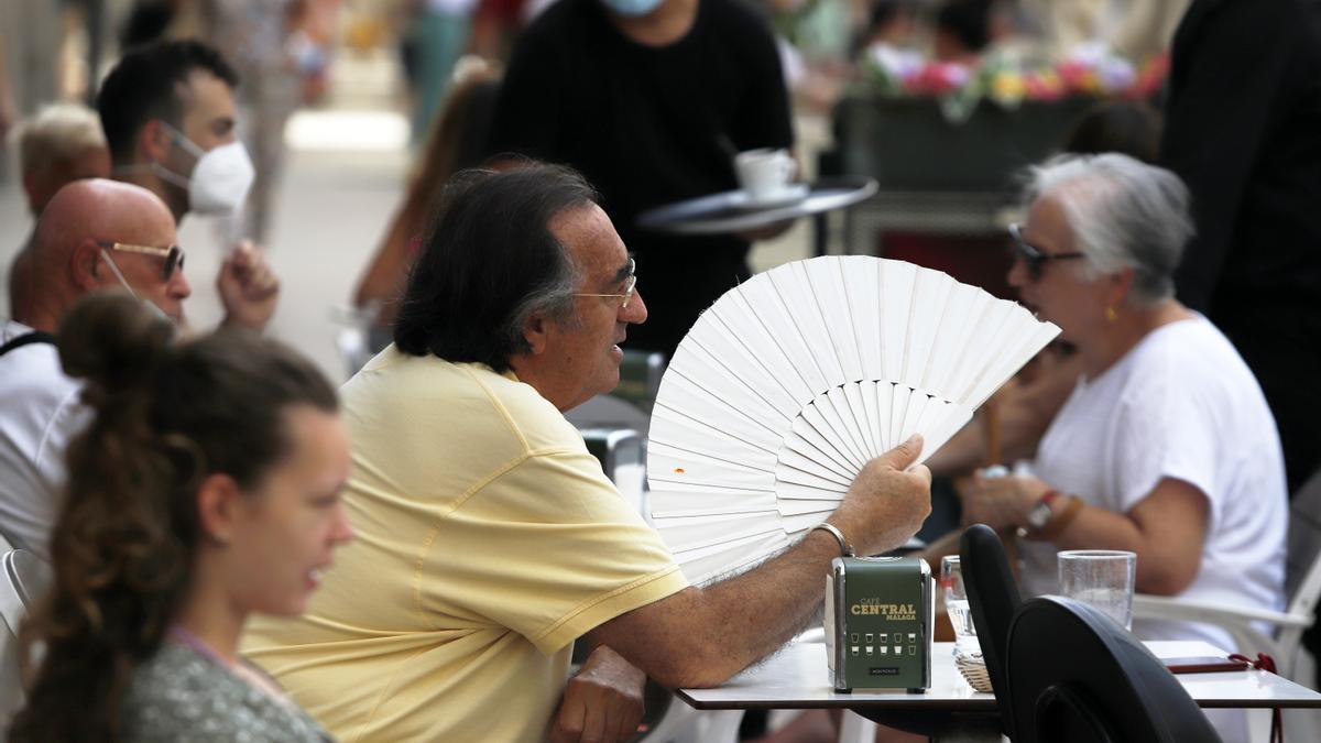 Varias personas intentan protegerse del calor en el día en foto de archivo.
