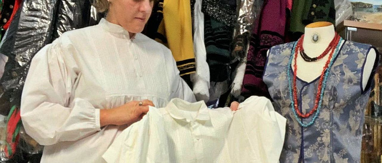 María Jesús Galán, con una camisa del traje de porruano, en su establecimiento de Cue, en Llanes.   Eva San Román