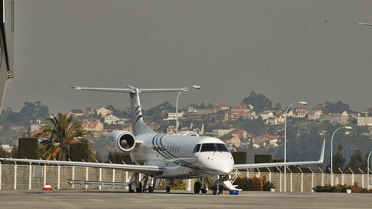 Un avión en la pista de Alvedro y, al fondo, núcleos de viviendas. |   // VÍCTOR ECHAVE