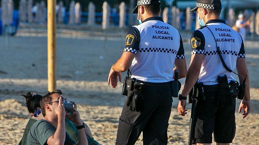 Un hombre se coloca la mascarilla en presencia de la Policía Local de Alicante en el Postiguet. | RAFA ARJONES