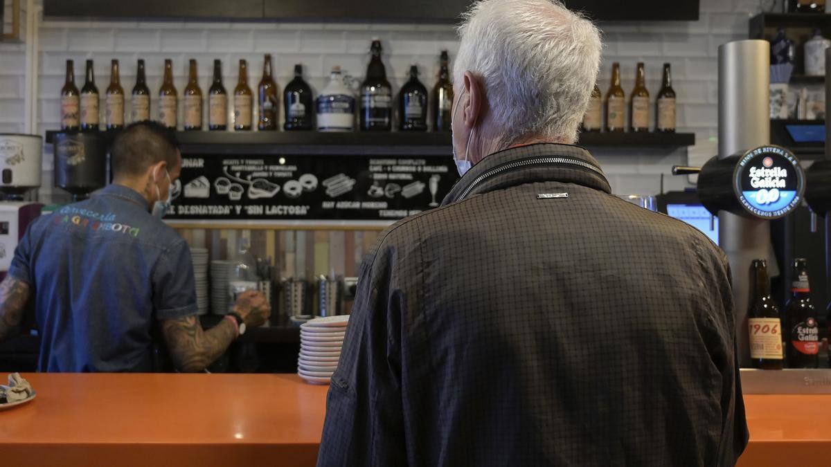 Cliente en la barra de un establecimiento en el primer día de nuevas medidas para la hostelería.