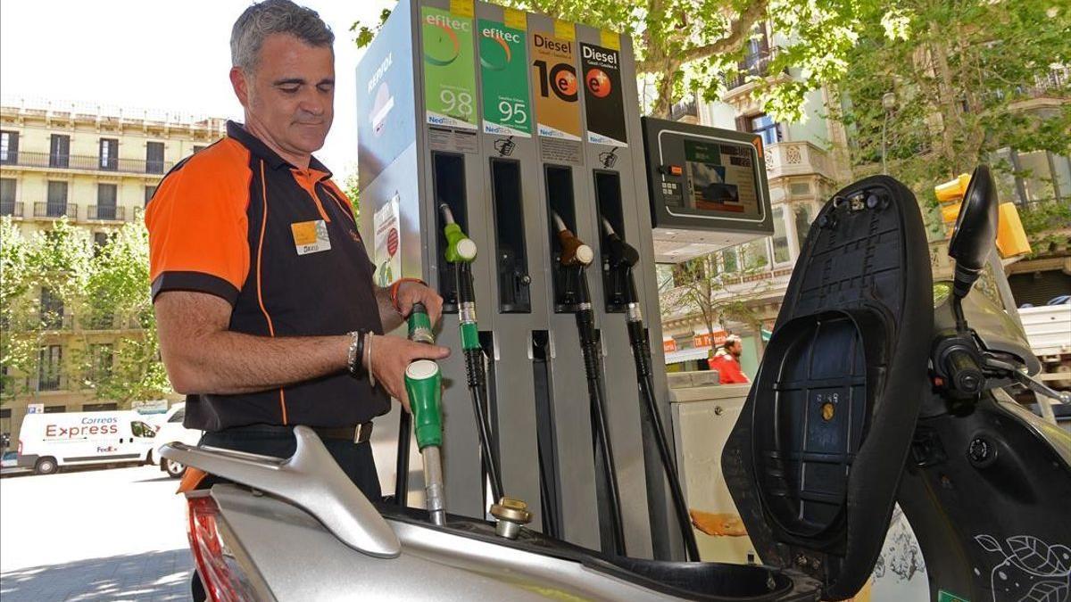 Un empleado de una estación de servicio en Barcelona reposta gasolina en una moto.
