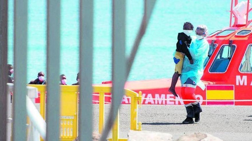 Una voluntaria de Cruz Roja lleva en brazos a un menor migrante que llegó el domingo a Fuerteventura.