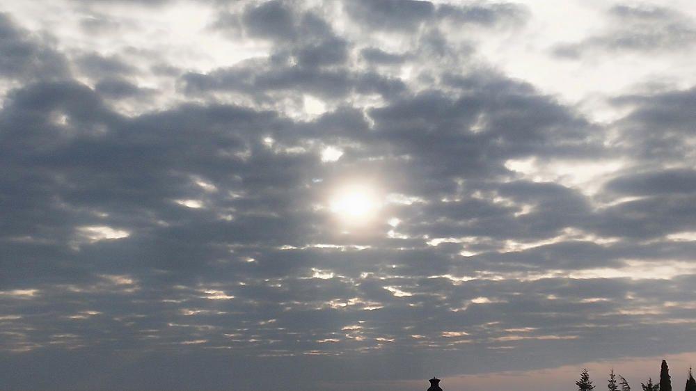El sol treu el cap per una finestra a Cardona.