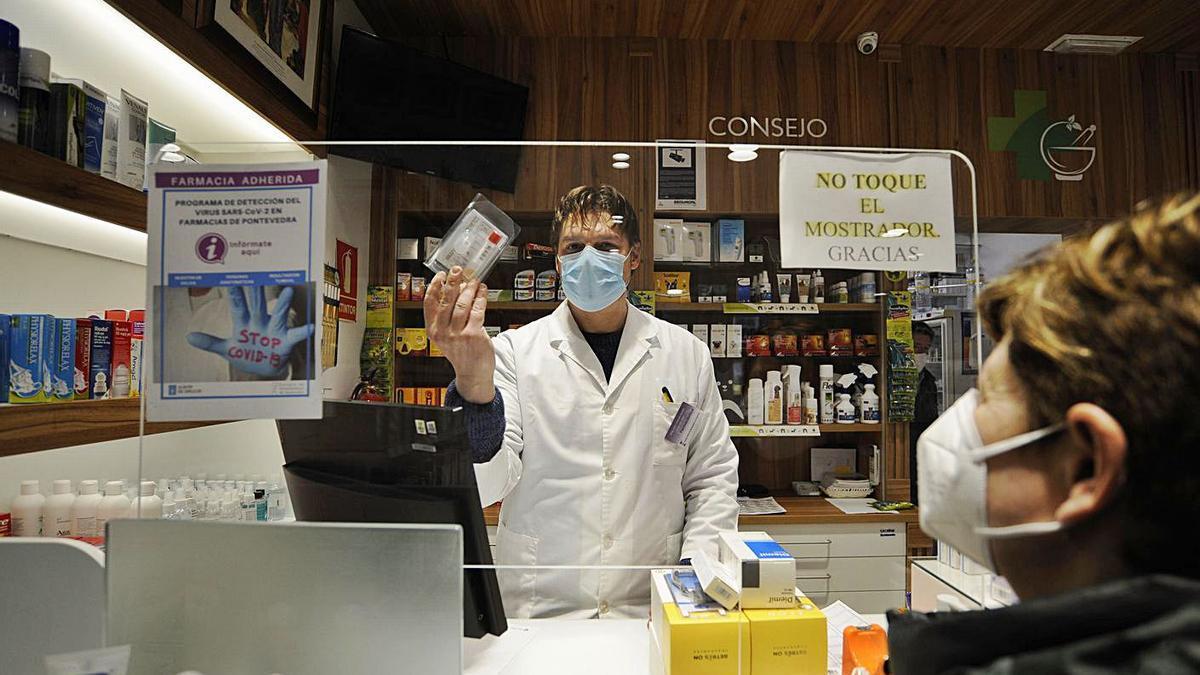 Personal de la Farmacia Garrido de Silleda muestra un test de saliva para detectar COVID.    // BERNABÉ / J. LALÍN