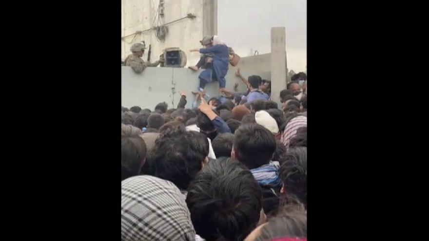 Soldados estadounidenses ayudan a una mujer afgana a saltar el muro del aeropuerto de Kabul