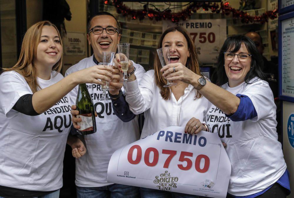 Trabajadores de la administración de la Avenida del Puerto, 173 en Valencia, celebran en su local que han distribuido parte del tercer premio del Sorteo Extraordinario de la Lotería de Navidad.