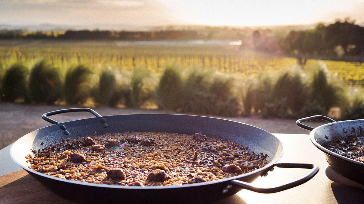 Dos dels arrossos que cuina Iolanda Bustos i al darrere les vistes que hi ha des del celler Mas Geli de Pals quan s'acosta la posta de sol