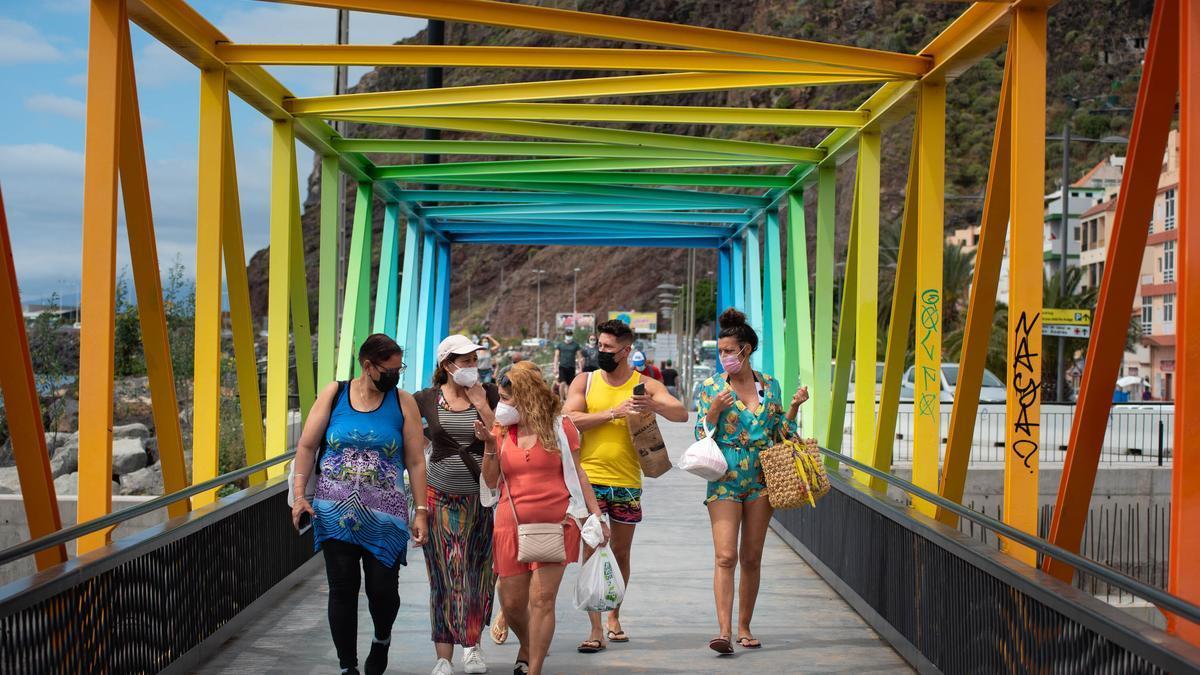 Unos bañistas se dirigen, por el puente de colores de San Andrés, a la playa de Las Teresitas.