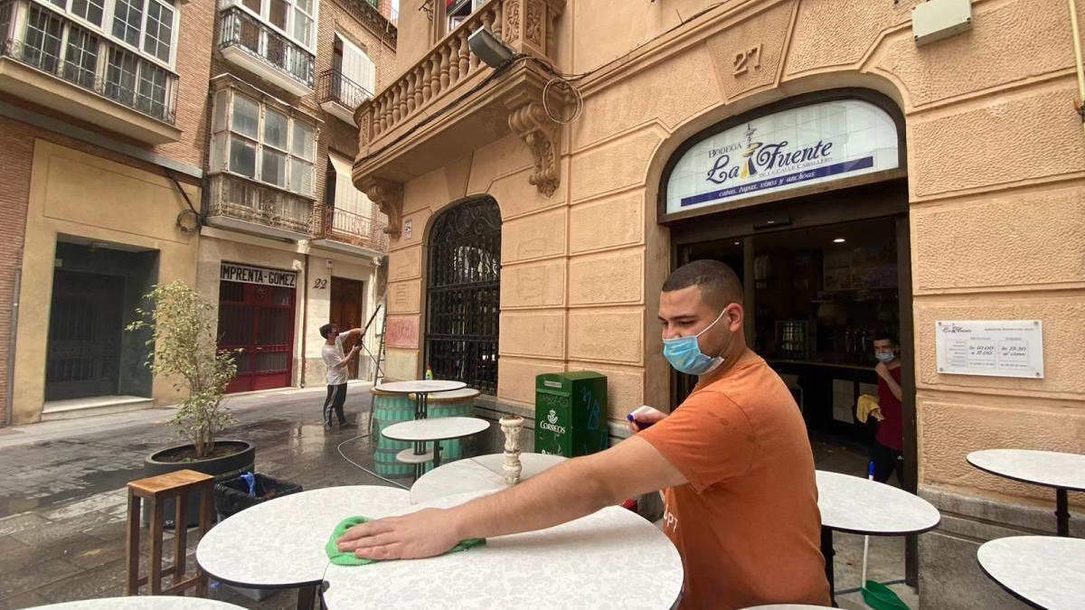 Un hombre limpia las mesas de una terraza en Cartagena.