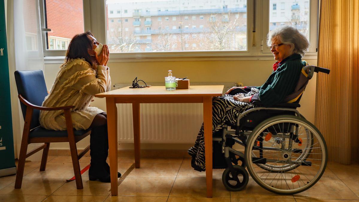 Imagen de archivo de una persona mayor que vive en una residencia recibiendo la visita de su hija.