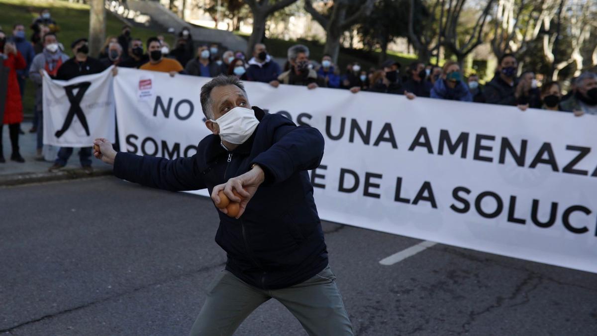 Un hombre lanza un huevo contra la sede de la Junta durante la protesta de la hostelería.