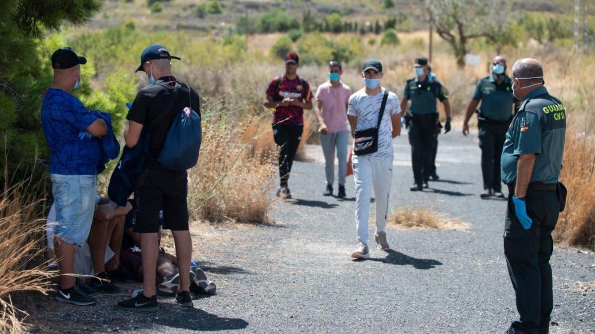 Agentes junto a jóvenes llegados en patera al Portús.