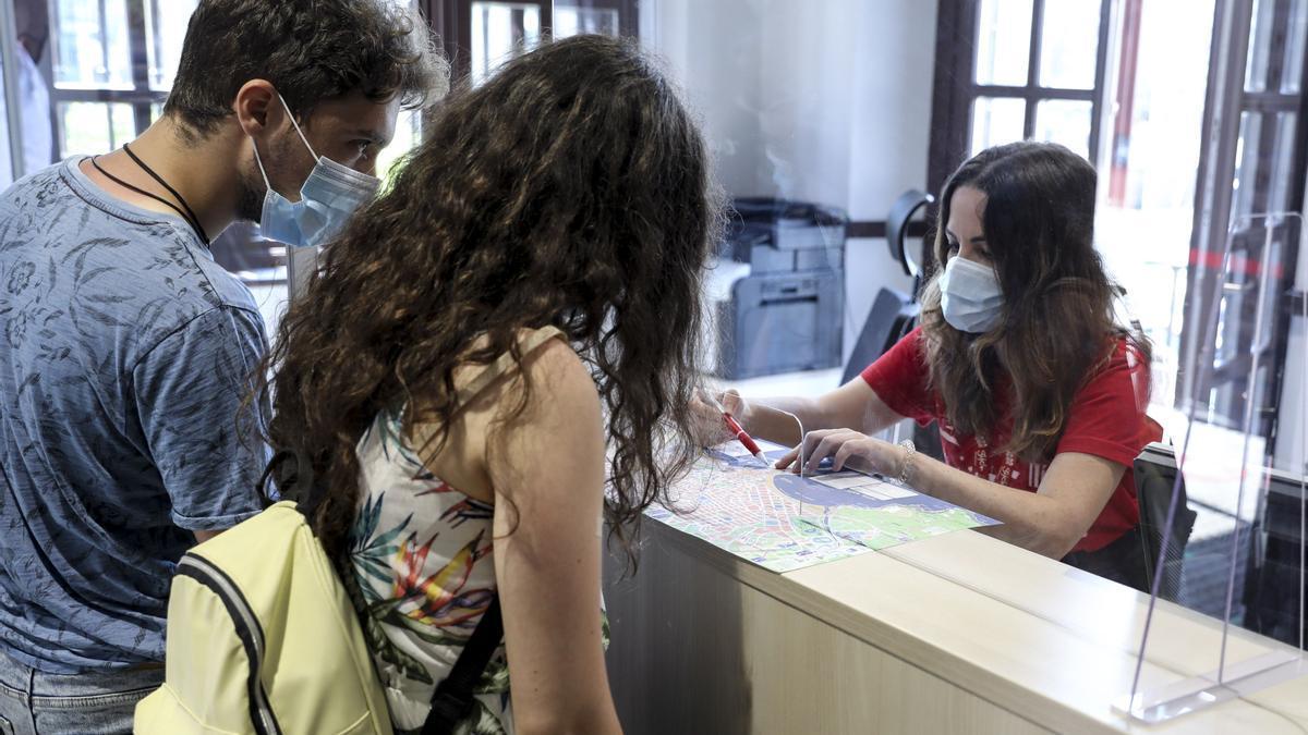 Dos turistas piden información en una oficina