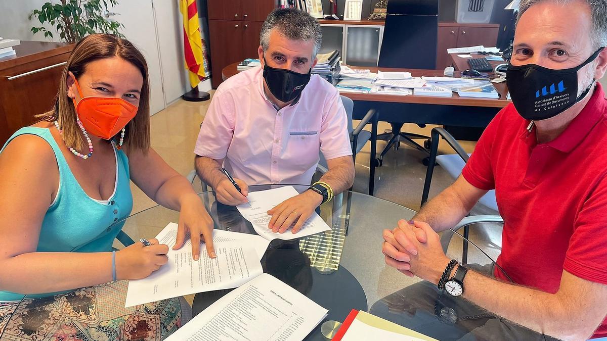 La representant de la família, Anna Coll, l'alcalde de Salt, Jordi Viñas, i l'arxiver municipal, Frederic Mayol en el moment de la signatura.
