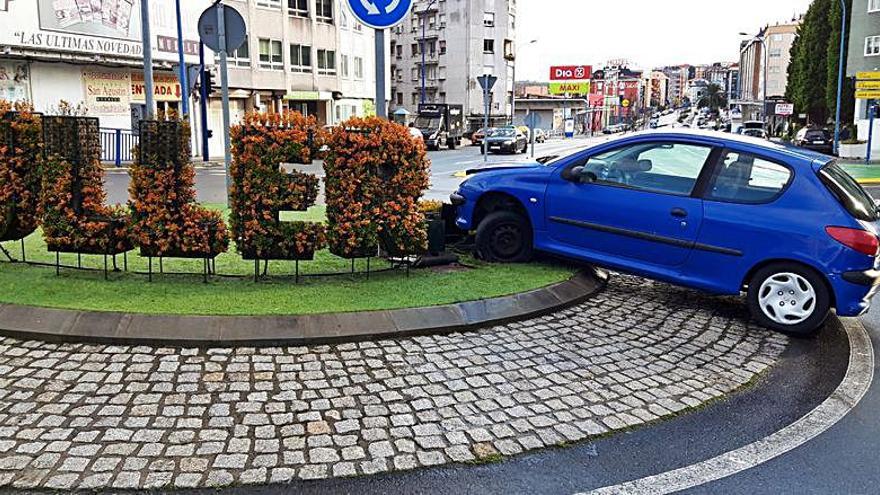 Un vehículo monta la rotonda de Fonteculler y derriba parte del letrero vegetal de 'Culleredo'