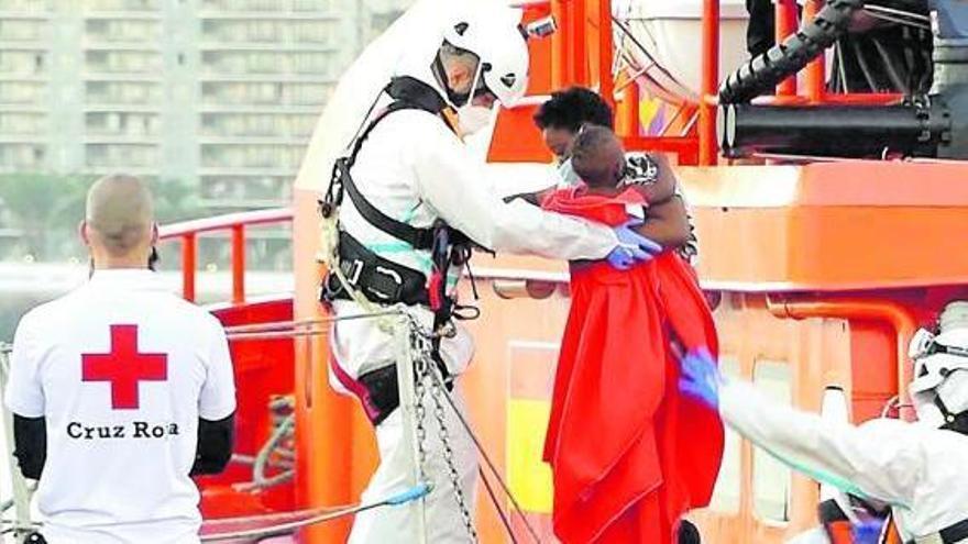 Un miembro de la Cruz Roja ayuda a bajar del barco a una mujer migrante con su niño en el puerto de Arguineguín.S