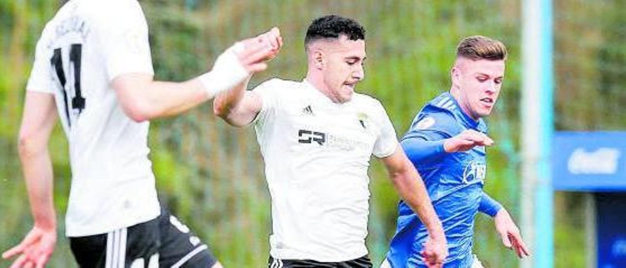 Sandoval, jugando con el Vetusta, presionado por Álvaro Rodríguez, del Burgos, con Elgezabal de espaldas. |