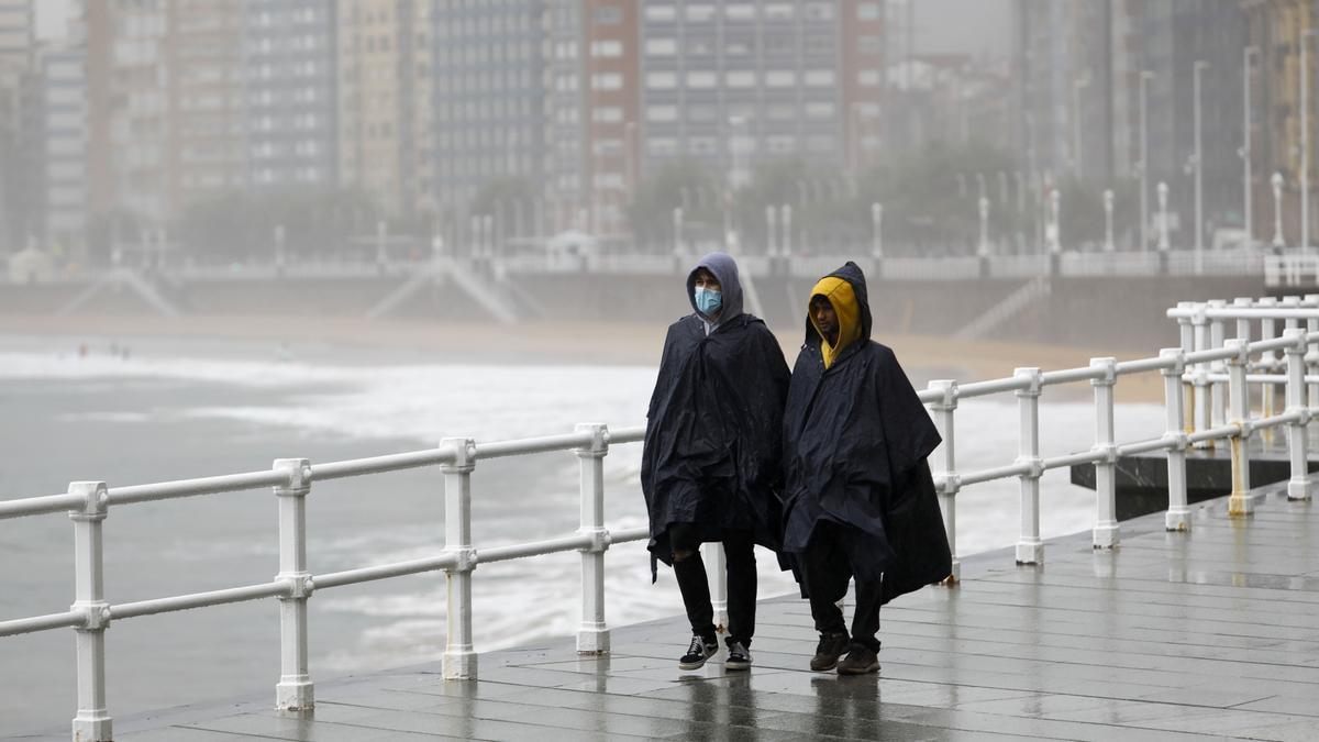 Dos paseantes se protegen de la lluvia en Gijón