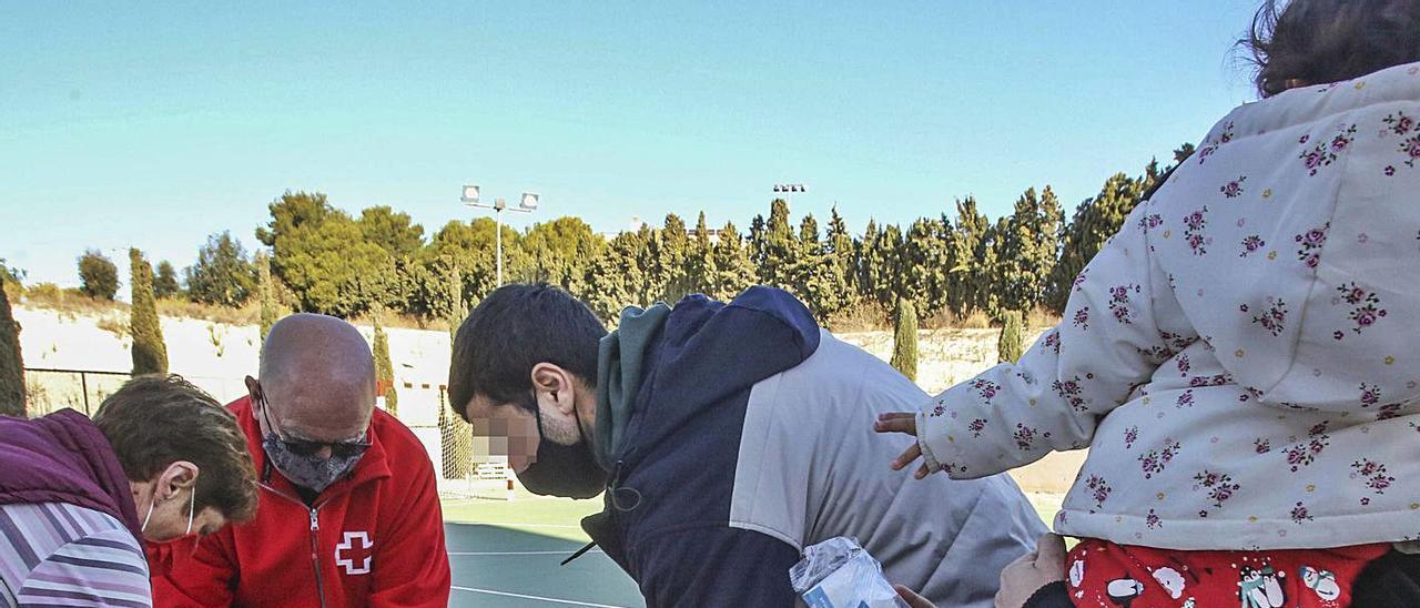 Una familia recoge alimentos en Cruz Roja de Alicante en el reparto realizado ayer.