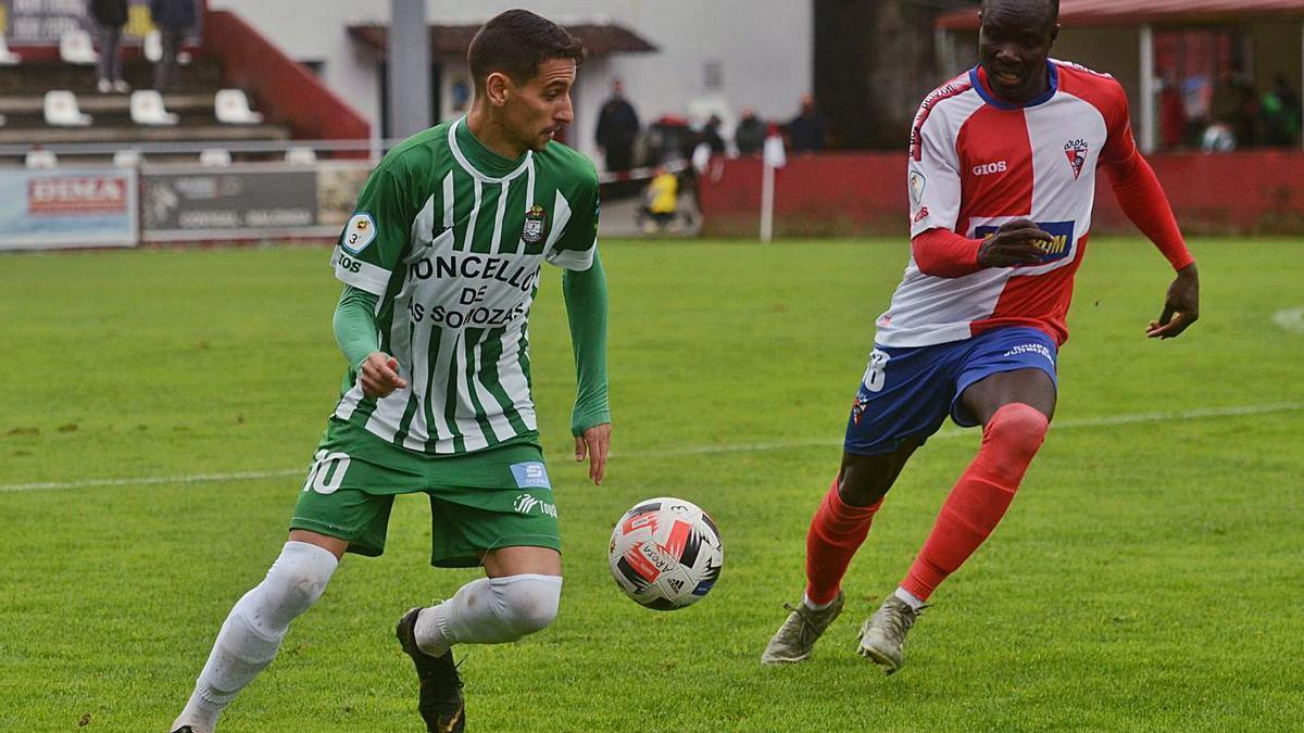 El delantero avilesino Nuño conduce el balón en el partido que decidió el ascenso en A Lomba. |