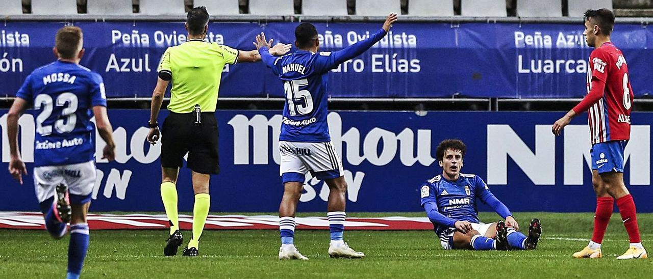 El árbitro Milla Alvendiz, de espaldas, señala el penalti por derribo a Sangalli, sentado en el césped, en el último derbi entre el Oviedo y el Sporting. |