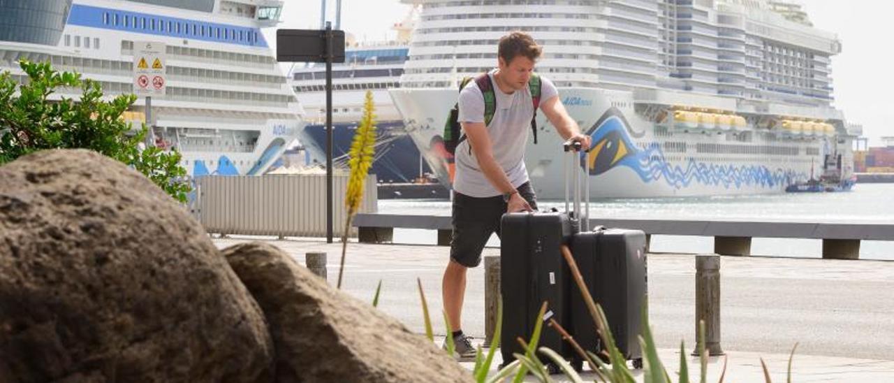 Un crucerista empuja sus maletas con varios barcos de AIDA atracados en el muelle Santa Catalina al comienzo de la pandemia, en marzo de 2020. | | TONY HERNÁNDEZ