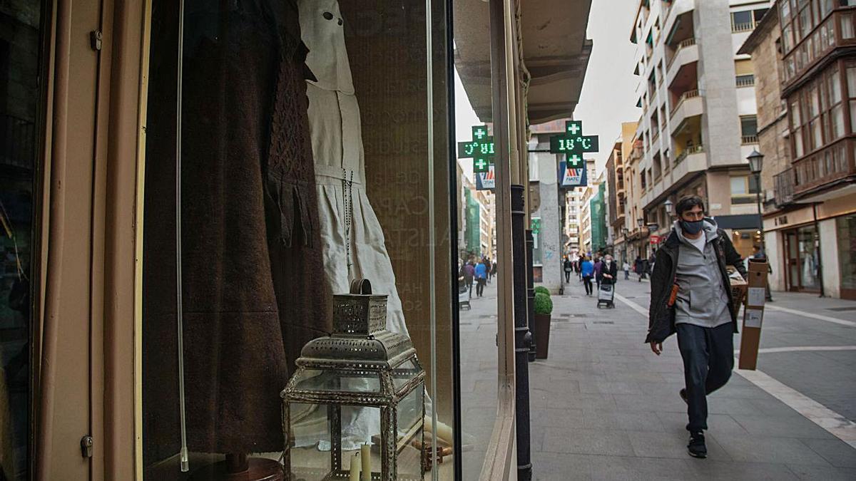 Trajes de la cofradía del Santo Entierro de Bercianos y un farol en el escaparate. | José Luis Fernández