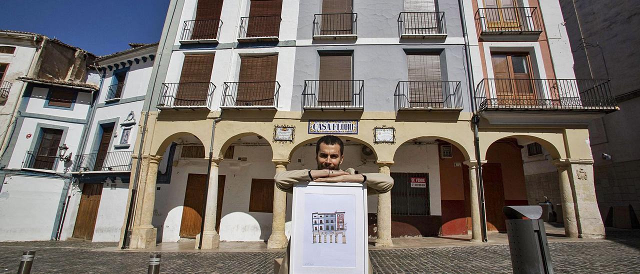 Juan Ignacio Barbieri posa con una de sus ilustraciones delante de la fachada que ha plasmado con su reconocible estilo. | PERALES IBORRA