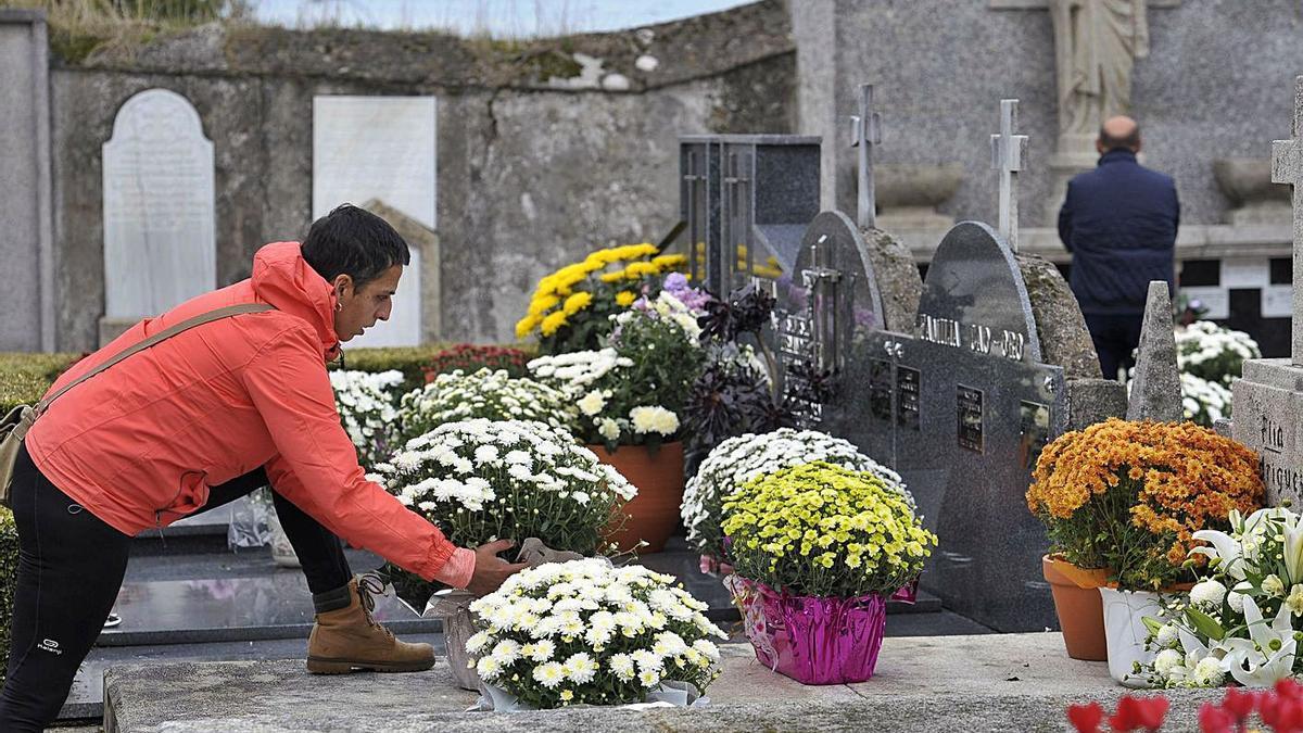 Un joven coloca flores en una sepultura del cementerio viejo de Lalín. |   // BERNABÉ