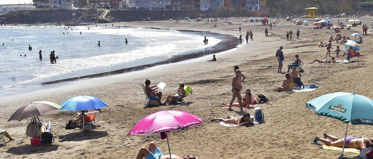 Decenas de sombrillas, casetas y toallas en la playa de Melenara, bien separadas las unas de las otras, en la playa de Melenara.