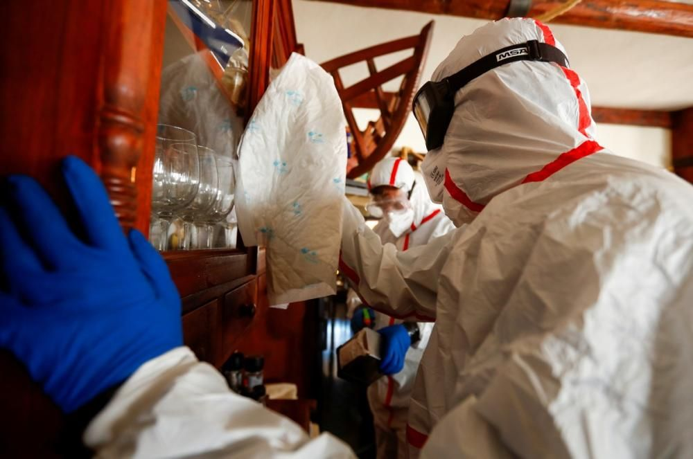 Sanitary workers disinfect a restaurant, as the ...