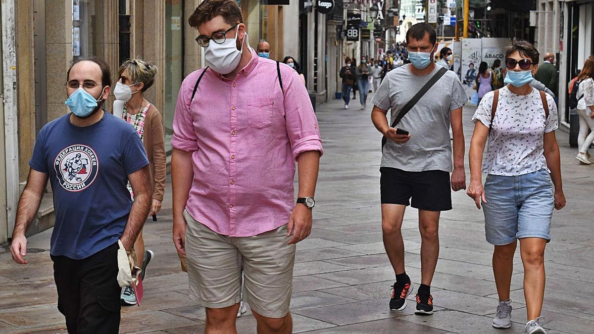 Ciudadanos con mascarillas pasean por la calle Real de A Coruña. |  // VÍCTOR ECHAVE