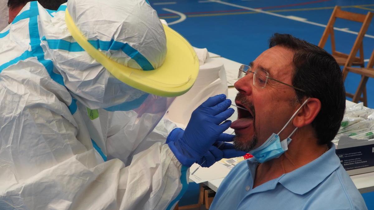 Pla detall d'un home fent-se la PCR amb un tècnic sanitari.