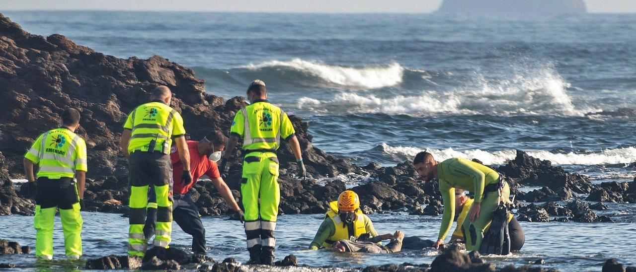 Efectivos de los servicios de emergencia rescatan un cadáver en la zona de Órzola en la que zozobró la patera la noche anterior.