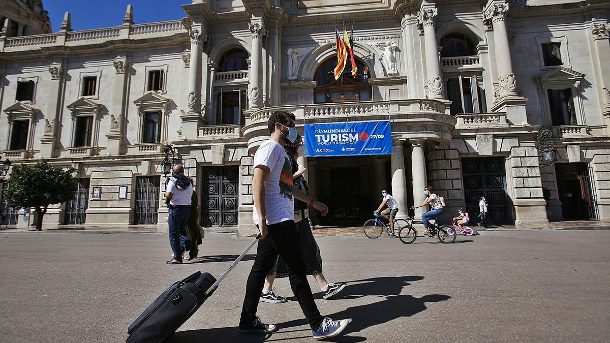 Unos turistas por delante de la puerto del ayuntamiento en el pasado Día Mundial de Turismo (27 de septiembre).   EDUARDO RIPOLL