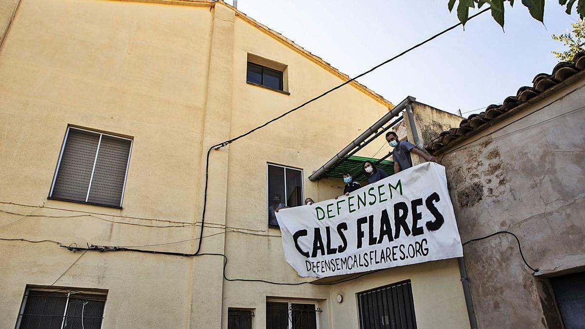 Un grupo de usuarios del centro social y cultural Cals Flares colgando una pancarta.  