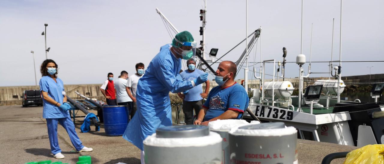 El enfermero Alberto Alonso toma una muestra nasal al pescador Pablo Rodríguez.