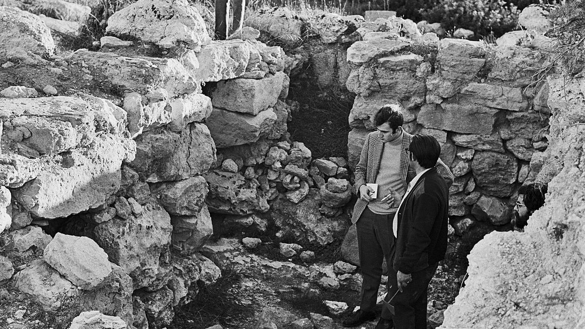 Arriba, el arqueólogo Guillem Rosselló Bordoy explica las tareas de excavación. Abajo, vista general del poblado prehistórico de Son Oms, en primer término se ve el túmulo con las habitaciones adyacentes. | LORENZO / LLEGAT GASPAR RIERA/ MUSEU DE MALLORCA