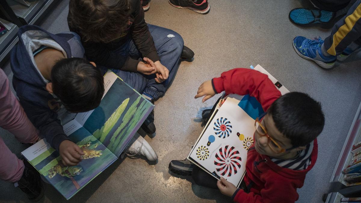 Varios niños leen libros prestados a través del servicio de bibliobús