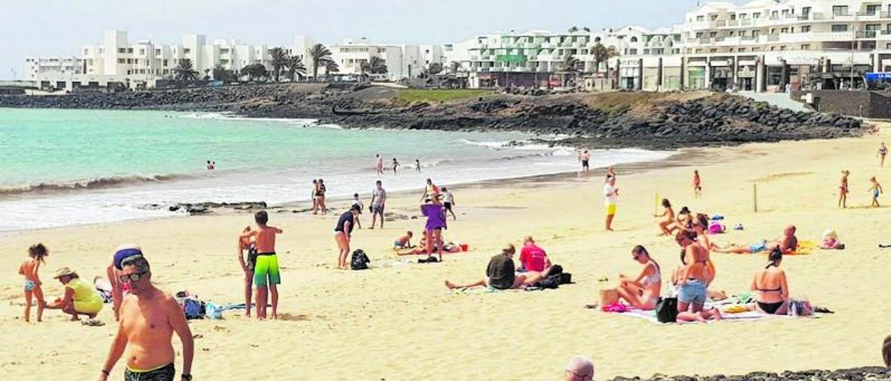 Bañistas, el pasado viernes, en la Playa de Las Cucharas, en Costa Teguise. Al fondo, tres de los establecimientos hoteleros que ya han reanudado su actividad.  | | A. F.