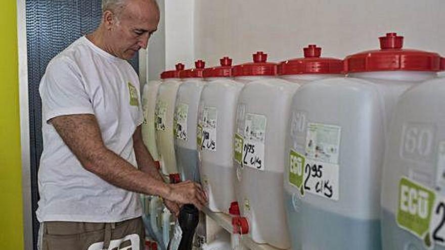 Carlos Hernández rellena uno de los botes de jabón.
