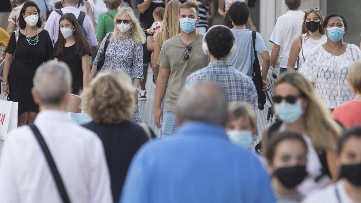 Gente con mascarillas en el centro de València.