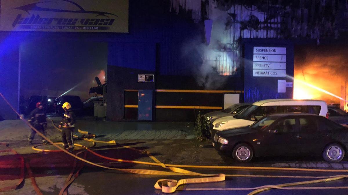 Los bomberos, durante su intervención en la extinción del incendio en Auto Talleres Vasi.