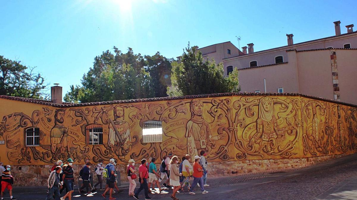 Un grupo de turistas observa detenidamente el nuevo mural de arte urbano en pleno Casco Histórico.   Cedida