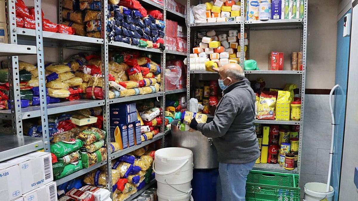 Voluntario preparando una cesta de comida para llevar.