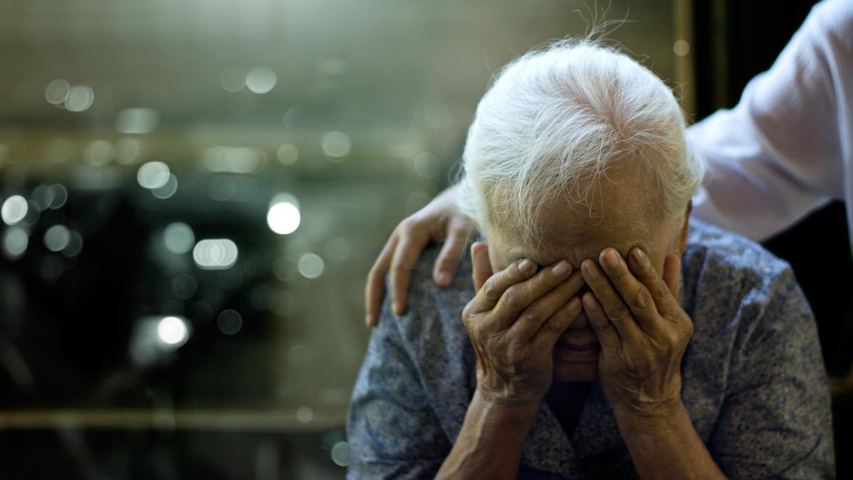 Una mujer con alzheimer es reconfortada por otra persona