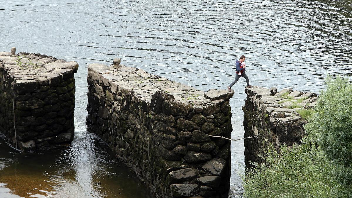 Un hombre pasea por las pesqueiras del Miño, en Arbo (archivo) // Marta G. Brea