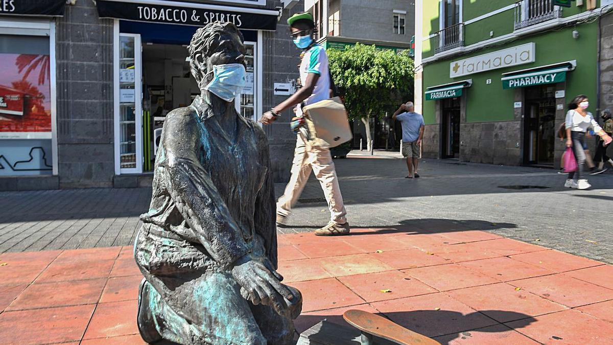 Una escultura del Paseo de Las Canteras, ataviada con una mascarilla.
