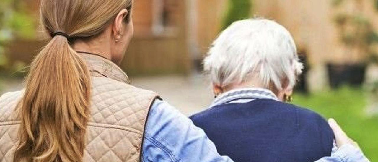 Una mujer acompaña a su pariente en un paseo por su residencia. | LEVANTE-EMV